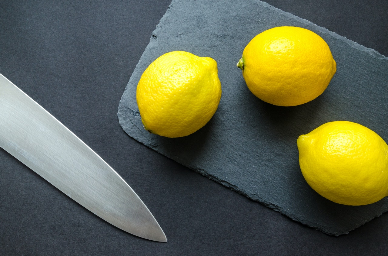 photo of three lemons on chopping board near knife 952369